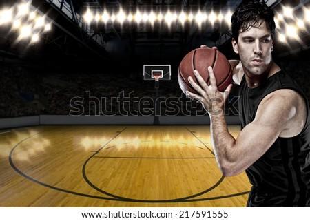 Basketball player on a  black uniform, on a basketball court. - stock photo