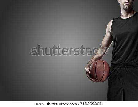 Basketball player on a  black uniform, on a black background. - stock photo