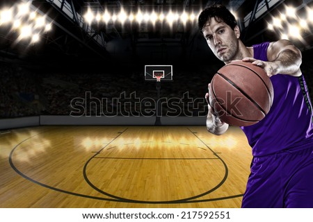 Basketball player on a  purple uniform, on a basketball court. - stock photo