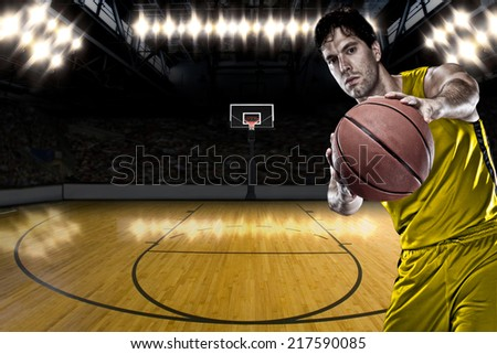 Basketball player on a  yellow uniform, on a basketball court. - stock photo