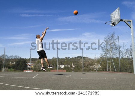 Basketball player shooting the ball on an outdoor court on a bright sunny day - stock photo