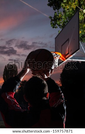 Basketball player silhouette at sunset - stock photo