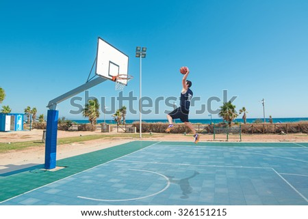 basketball player slam dunk in a blue playground - stock photo