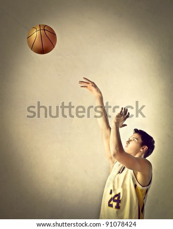 Basketball player throwing a ball - stock photo