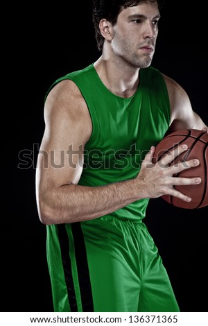 Basketball player with a ball in his hands and a green uniform. photography studio. - stock photo