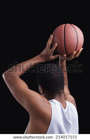 Basketball player with ball on black background