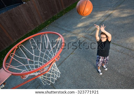 basketball practice for a young boy at home - stock photo
