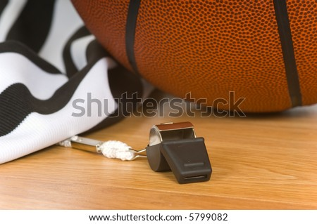 Basketball referee items including a whistle, a jersey and a basketball on a gym floor - stock photo