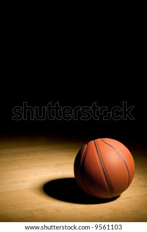 basketball resting on the hardwood floor in the spotlight with black copy space above - stock photo