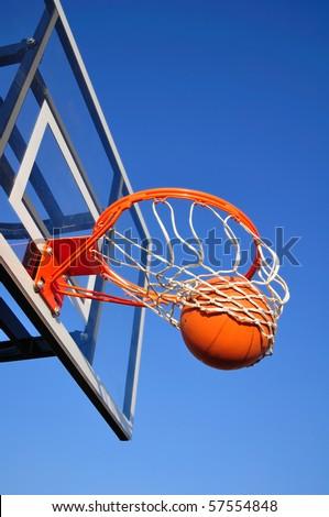 Basketball Shot Falling Through the Net, Blue Sky, vertical, copy space - stock photo
