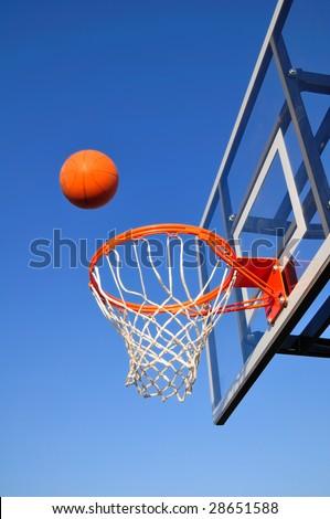 Basketball Shot Heading Toward the Hoop, Blue Sky, vertical, copy space - stock photo