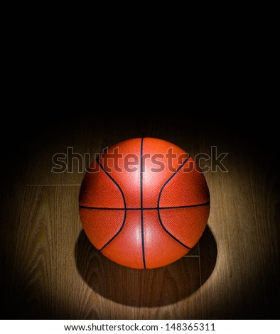 Basketball under spotlight on Gym Floor - stock photo
