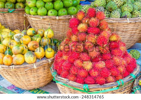 Baskets at a street market full of tropical fruit: rambutan, passion fruit, sapote, chirimoya, lime - stock photo