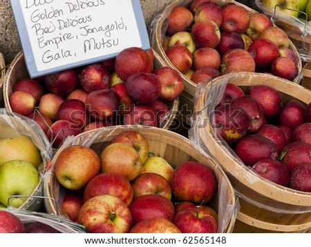 Baskets of apples on display with sign at the local farmers outdoor maket - stock photo