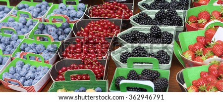 Baskets of Fresh Berries at Fruit Market with natural ripe colorful nutritious blackberries strawberries and blueberries - stock photo