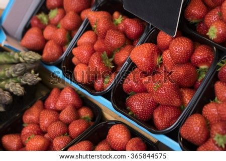 Baskets of fresh bright red seasonal strawberries on market stand for sale - stock photo