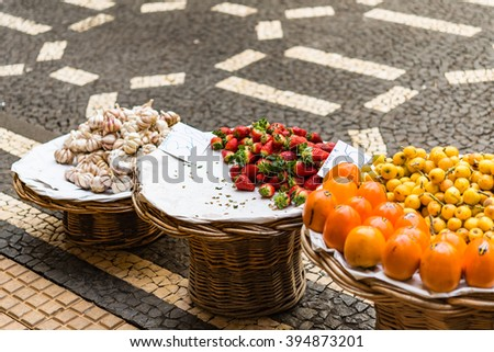 Baskets of neatly arranged fruit at farmers market.  Three round display baskets of neatly arranged fruit for sale on street market in Madeira Portugal - stock photo