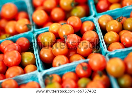 Baskets of red cherry tomatoes for sale at a farmer's market. - stock photo