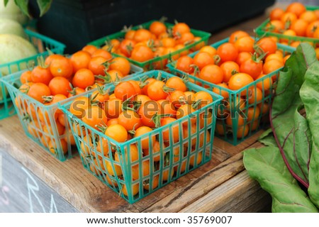 Baskets of small orange cherry tomatoes on display for sale at the farmers market - stock photo