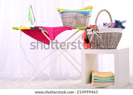 Baskets with laundry and ironing board on light home interior background - stock photo