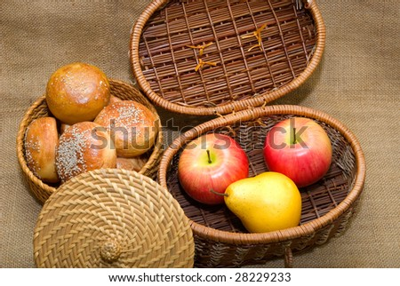 Baskets with rolls and fruits are photographed on an old fabric - stock photo
