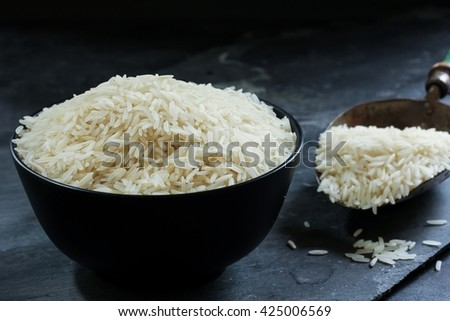 Basmati rice bowl, Cooked basmati rice in a black bowl on dark moody background, selective focus