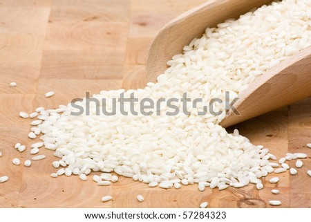 Basmati rice in wooden scoop on table