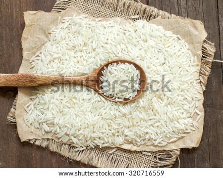 Basmati rice with a spoon on an dark wood - stock photo