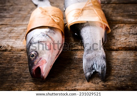 Bass fish head and tail on wooden background,selective focus  - stock photo