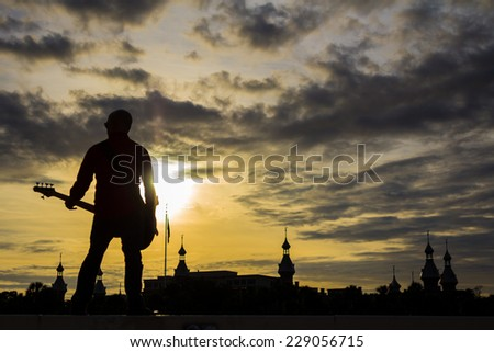 Bass guitar player against sunset background - stock photo