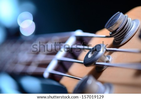 Bass guitar with focus on bottom E string and string-tree. - stock photo