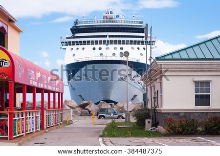 BASSETERRE,ST. KITTS AND NEVIS- APRIL 4,2011: Celebrity Summit cruise ship docked at Basseterre harbor at St. Kitts during a west caribbean itinerary. At he front, there is a house and restaurant. - stock photo
