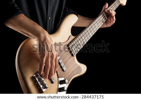 bassist playing a custom made  bass guitar on black background