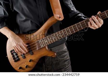bassist playing bass guitar made of exotic wood