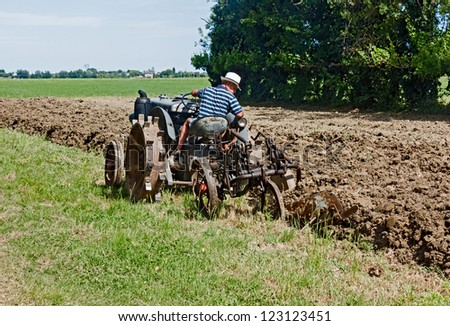 "BASTIA, RAVENNA, ITALY - MAY 29: unidentified farmer plow the land with an old tractor during the recall of the old farm work ""ricordando i vecchi tempi"" on May 29, 2011 in Bastia, Ravenna, Italy"
