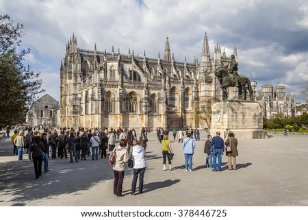 Batalha, Portugal - April 05, 2015: Tourists gathering around for a guided tour of the monastery. UNESCO World Heritage Site. - stock photo