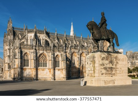 BATALHA, PORTUGAL - FEBRUARY 3: lateral view of the Batalha monastery, also known as the Monastery of Saint Mary of the Victory, and statue of Nuno Alvares Pereira in Portugal, on February 3, 2016.