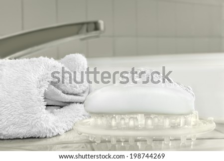 Bath accessories on shiny porcelain tile. Clean relaxing bath concept. Wet bar soap and bubbles on clear plastic dish, white fluffy soft bath towel. Tub faucet in blurred background.   - stock photo