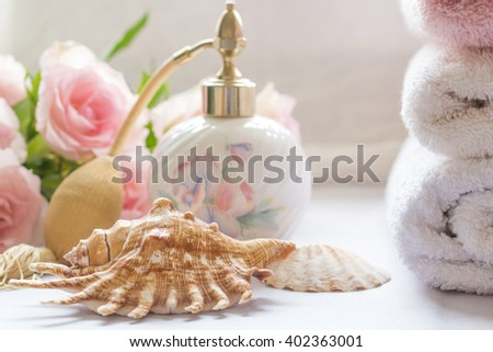 Bath arrangement with parfume bottle, folded towels and pink roses