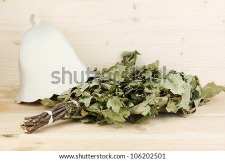 Bath broom of oak and hat on wooden background - stock photo