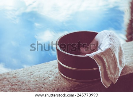Bath bucket with a towel at a hot spring bath at Japanese onsen. Filtered image.  - stock photo