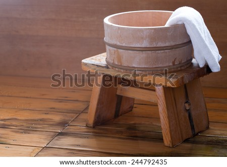 Bath bucket with a towel on a wooden stool at a blurred Japanese onsen room