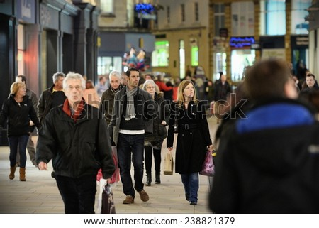 BATH - DEC 19: People walk along a street in the city's shopping district on Dec 19, 2014 in Bath, UK. Stores reported busy trade with only 5 days left of Christmas shopping season. - stock photo
