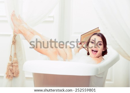 Bath fun. Side view of beautiful playful young woman holding a book and lauphing while enjoying bubble bath - stock photo