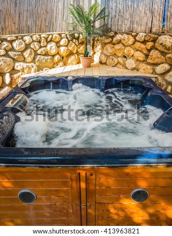 Bath - Jacuzzi in the garden. Water bath boiling - stock photo