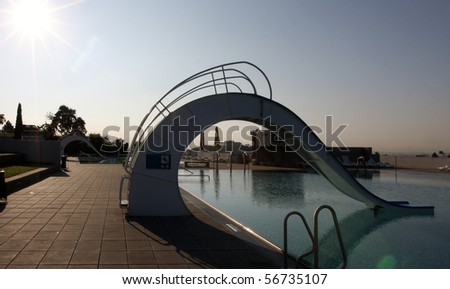 Bath pool with white slide during a sunset - stock photo