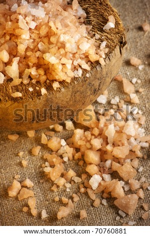 Bath salt in coconut shell and spilled on burlap.