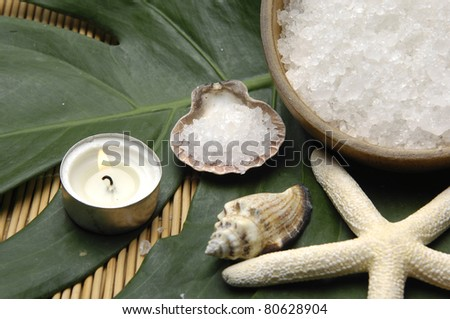 bath salt in seashell with candle and monstera leaf on woven mat - stock photo