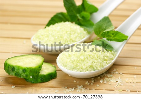 Bath salt in white ceramic spoons with mint and cucumber on wooden surface. Shallow DOF, focus on front spoon. - stock photo