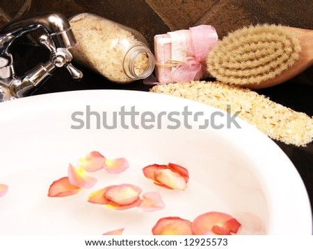 Bath salt, soap and a wooden brush laying around a white ceramic sink with rose petals floating in the water - stock photo
